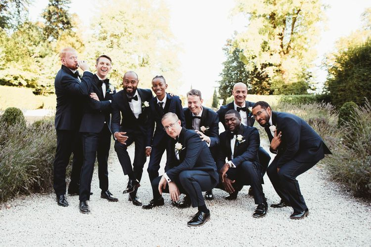 Groomsmen portrait in tuxedos for destination wedding with pink bridesmaid dresses