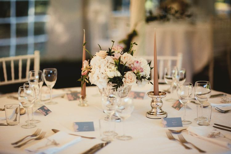 Elegant floral centrepiece and candlesticks for destination wedding with pink bridesmaid dresses