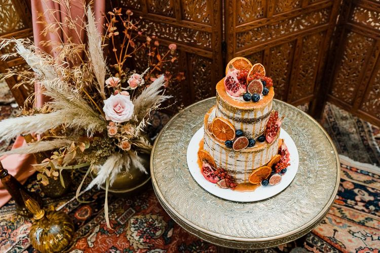 Drip Wedding Cake in Gold Platter with Dried Grass Floral Arrangement and Moroccan Rugs