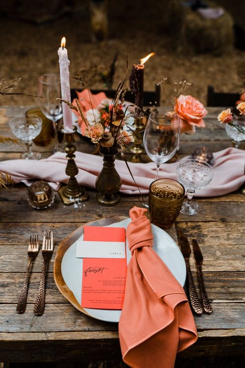 Place Setting with Gold Cutlery, Coloured Glass and Coral Napkin