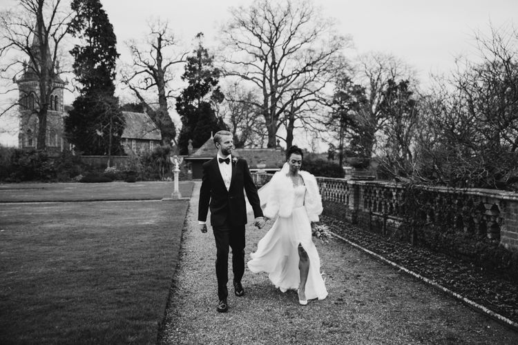 stylish bride and groom walking through the grounds at  The Elvetham wedding venue