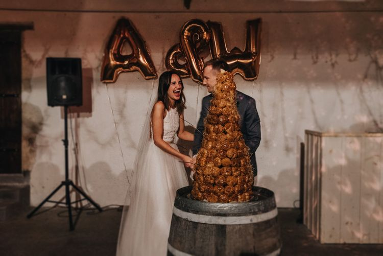 Bride and Groom cutting the Cake with Copper Foil Balloons Backdrop