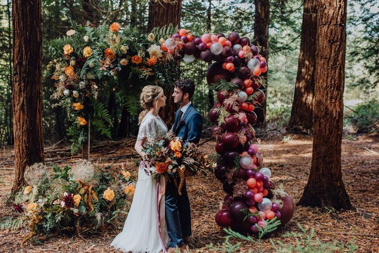Bride and Groom Standing in Front of an Autumnal Flower and Balloon Arch
