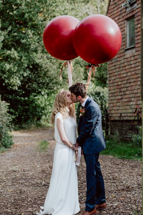 Bride and Groom Kissing Holding Extra Large Balloons