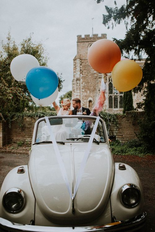 Bride and Groom in Convertible VW Beatle Holding Giant Bright Balloons