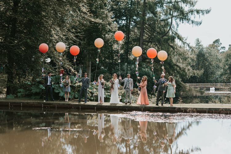 Wedding Party Portrait on the Rivers Edge with Everyone Holding a Giant Balloon on a String