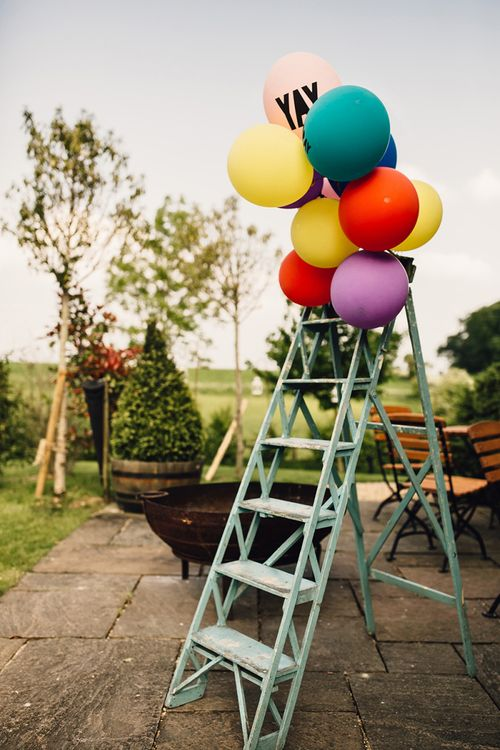 Colourful Balloons with YAY Slogan Balloon Tied to Vintage Step Ladders