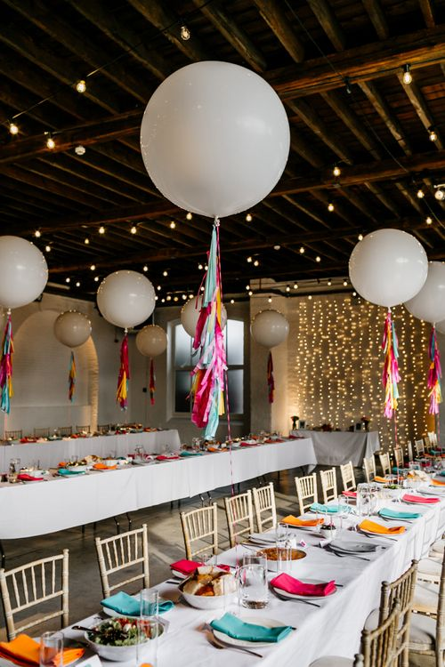 Industrial Wedding Venue Decorated with Fairy Light and Giant Balloons with Colourful Tissue Tassels