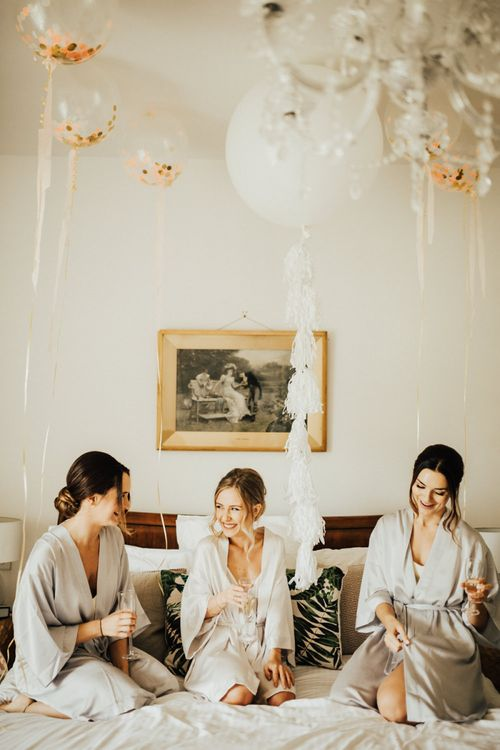 Bride and Bridesmaids on Wedding Morning with Oversized White Balloon with Tassels and Pink, Gold and White Confetti Balloons lining the ceiling