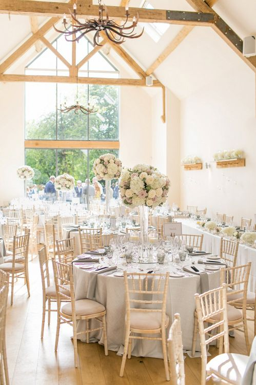 Light and airy round table reception at Millbridge Court with tall, pale floral centrepieces
