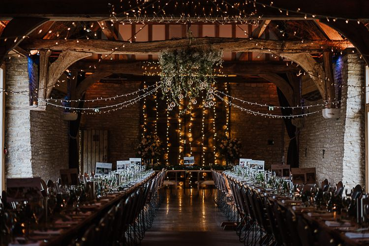 Tythe Barn Wedding Venue with candlelit long tables and hanging fairy lights