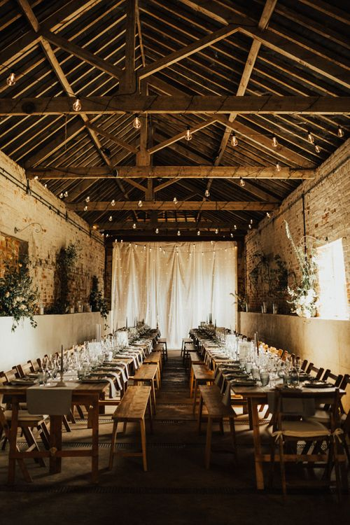 Festoons hanging in from exposed beams in Fishley Hallbarn above long table reception