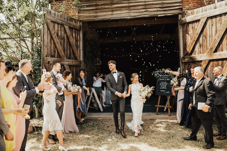 Bride and groom exiting ceremony at barn door under shower of confetti