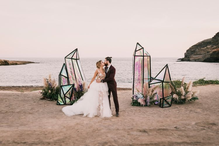 Beach weddings with irredecent geode wedding structures