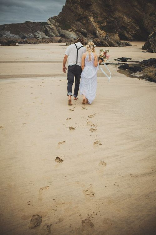 Bride and groom leaving footprints in the sand