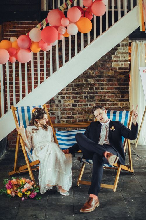Bride and groom sitting in deck chairs with balloon installation decorating the stairs