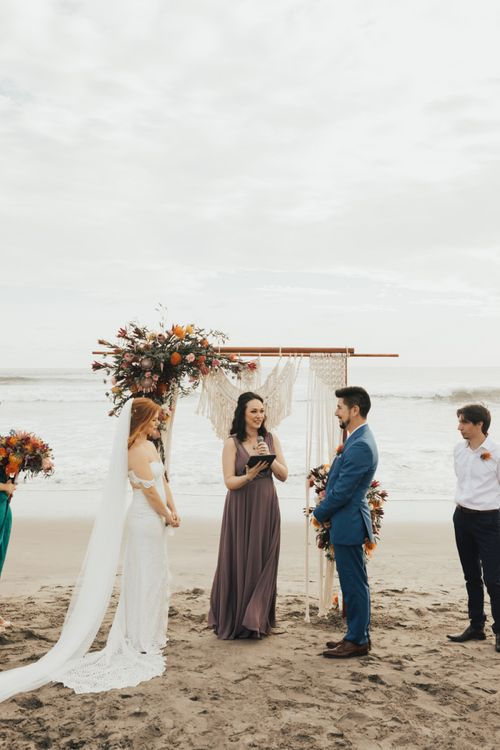Beach wedding ceremony with wooden frame altar