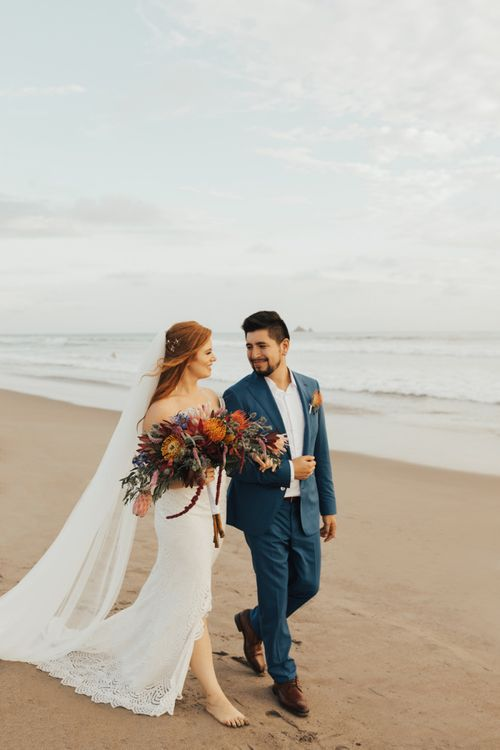 Bride and groom walking along the beach with orange wedding bouquet