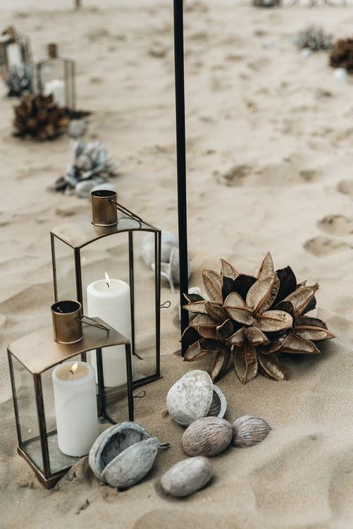 Bronze  lanterns and pebbles aisle decor