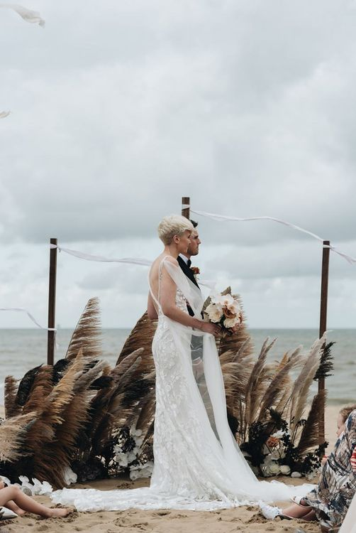 Bride and groom standing at the altar with dried grass floral arrangement