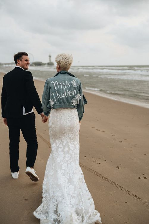 Bride and groom walking along their beach weddings with denim jacket