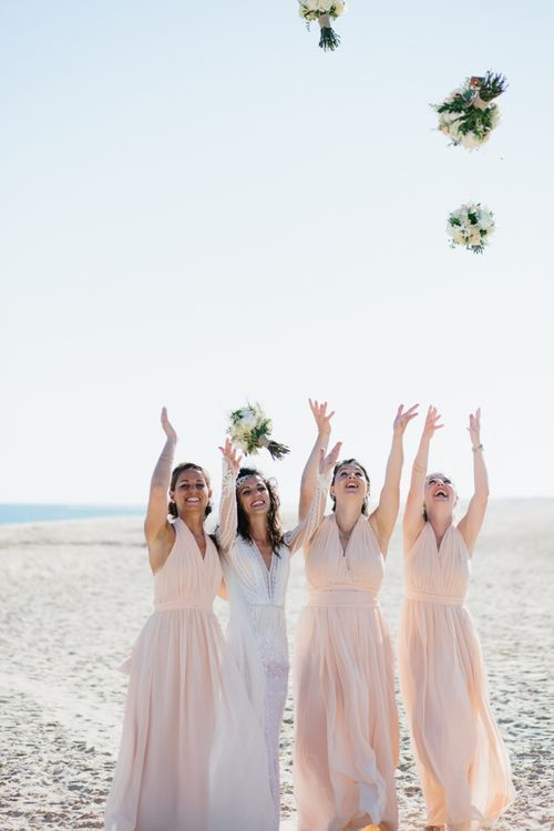 Bridesmaid throwing their bouquets in the air at beach wedding