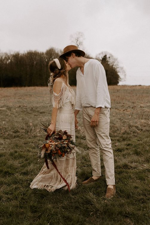 Boho Bride and Groom Kissing in a Field