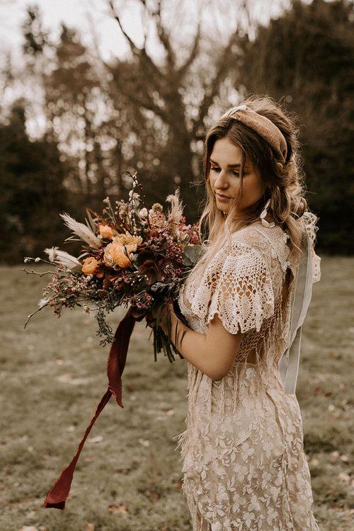 Boho Bride in Lace Wedding Dress Holding a Boho Wedding Bouquet