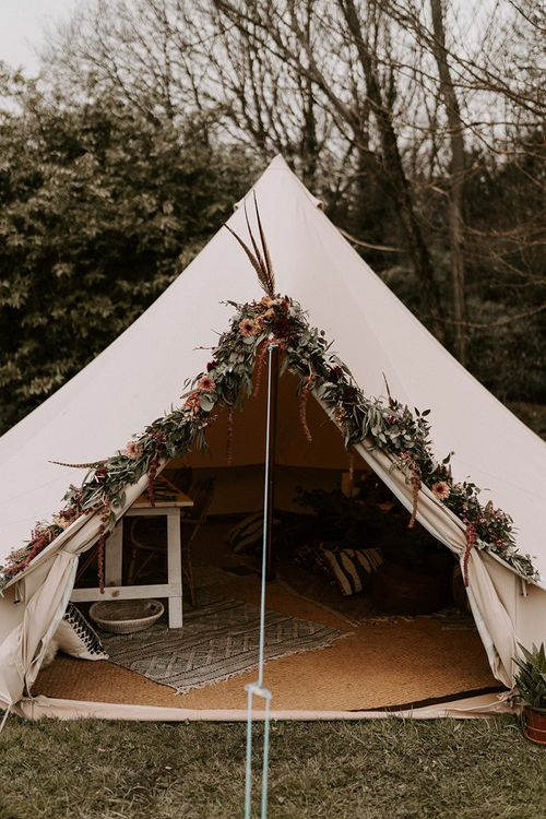 Bell Tent with Flower Covered Entrance and Cosy Seating Area Inside