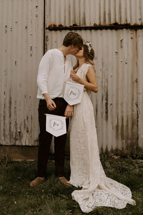 Boho Bride in Lace Wedding Dress and Groom in Casual Trousers and Shirt Holding Up Mr & Mrs Banners