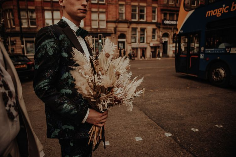 Groom in patterned suit holding a dried flower wedding bouquet