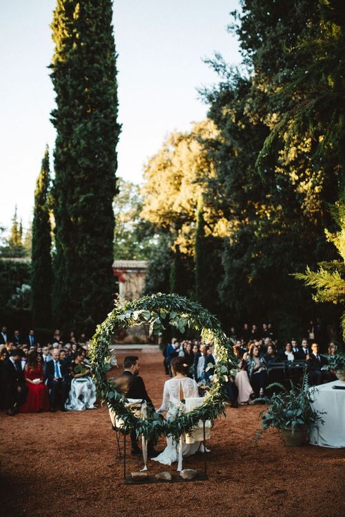 Bride and Groom Sitting in Front of a Foliage Moon Gate Altar for Outdoor Wedding Ceremony