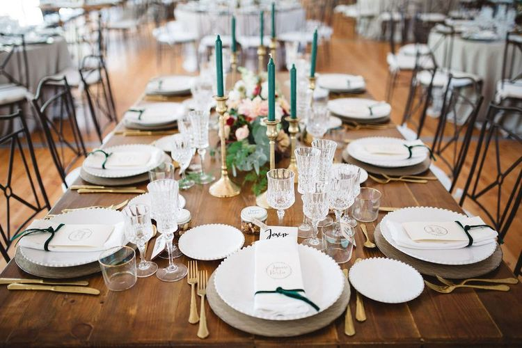 Elegant Table Setting with Gold Candlesticks and Green Taper Candles