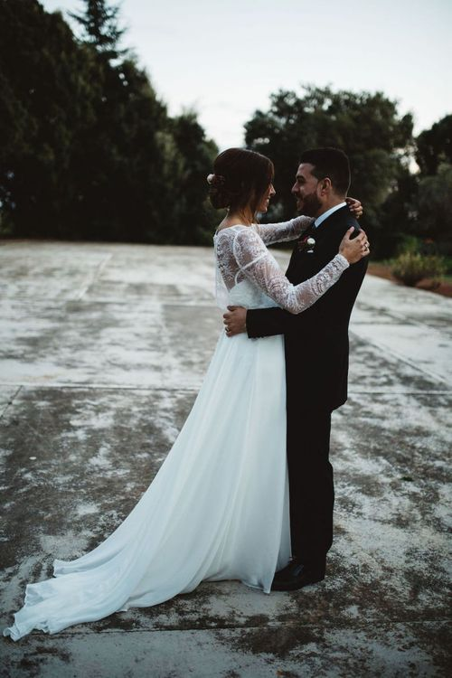 Bride in Jordi Anguera Wedding Dress with Lace Overlay and Groom in Señor Suit  Embracing