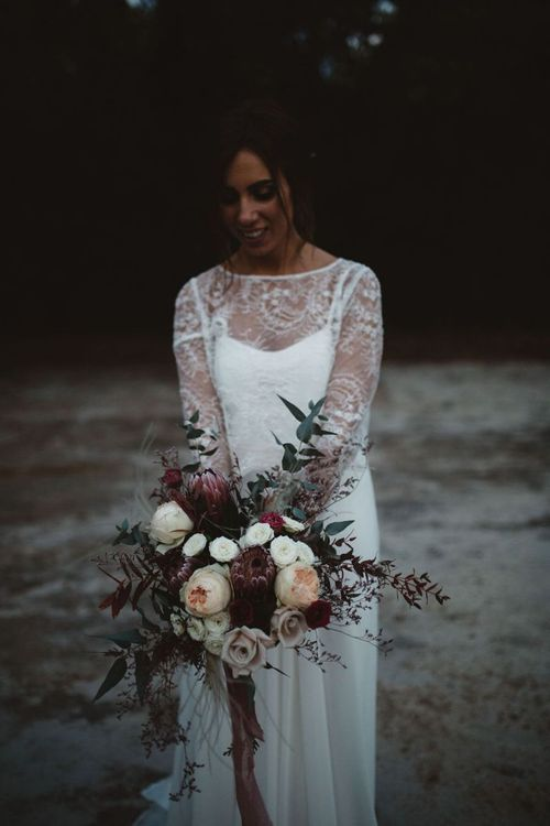 Bride in Jordi Anguera Wedding Dress with Lace Overlay Holding a Deep Purple, White and Green Bridal Bouquet with King Proteas