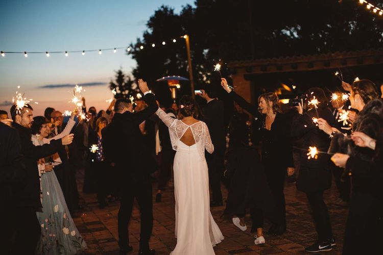 Bride and Groom Holding Hands During Sparkler Moment