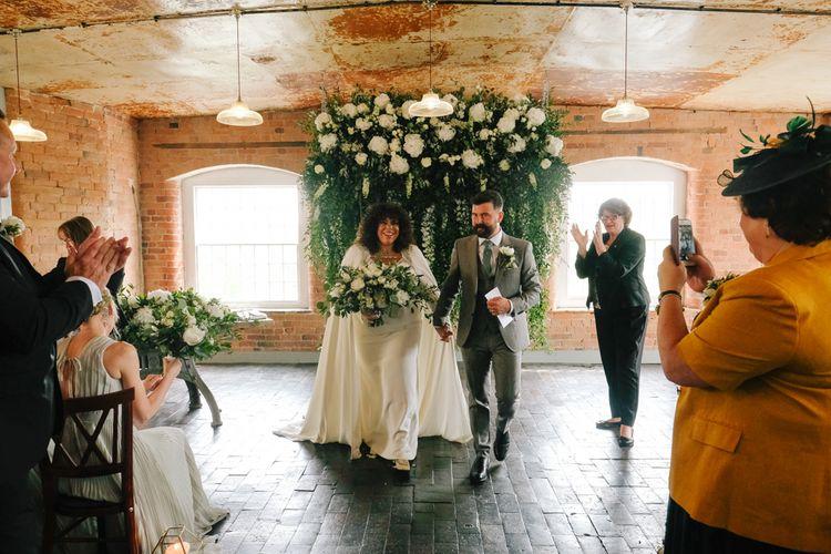 Stylish black bride in wedding cape for industrial wedding at West Derby Mill