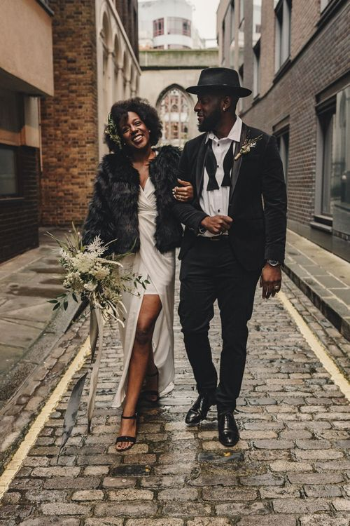 Stylish black bride in satin wedding dress and faux fur cover up and groom in bow tie and hat