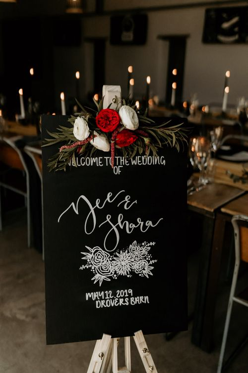 Black Wedding Welcome Sign with White Font and Red & White Floral Decor