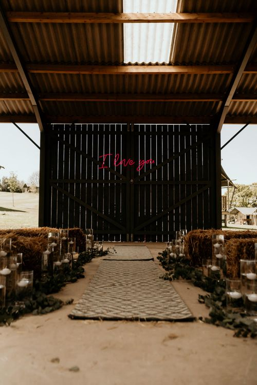 Barn Wedding Ceremony with Hay Bales and Pink Neon I Love You Sign