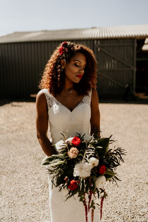 Black Bride with Afro Hair in Lace Wedding Dress Holding a Red and White Wedding Bouquet