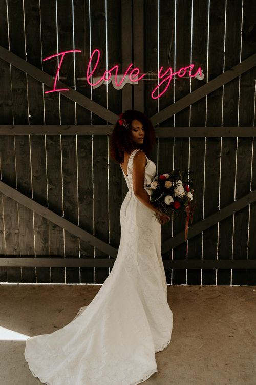 Black Bride with Afro Hair in Lace Wedding Dress Holding a Red and White Wedding Bouquet Under a Neon Wedding sign