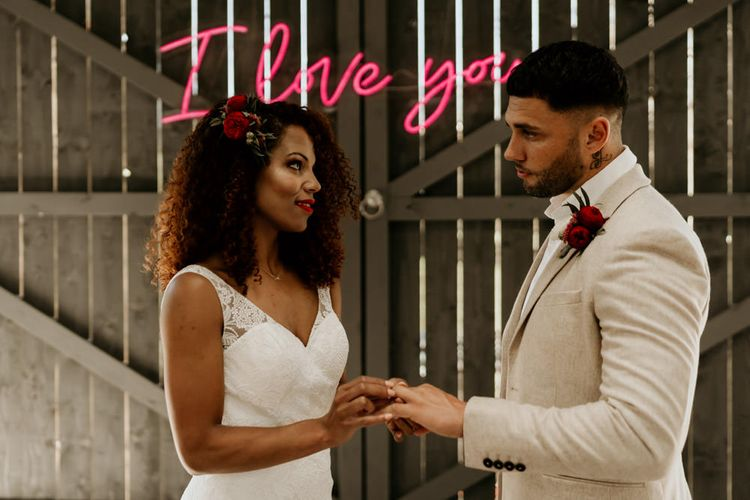 Black Bride with Afro Hair in a Lace Wedding Dress and Groom in Blazer Exchanging Vows Under a Neon Wedding Sign