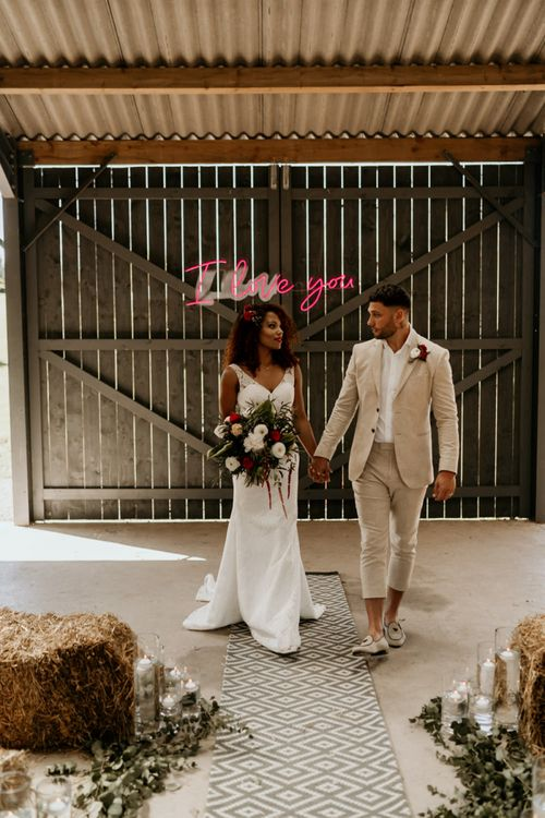 Black Bride with Afro Hair in a Lace Wedding Dress and Groom in Blazer Walking up The Aisle Lined with Rugs