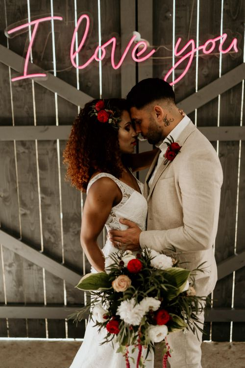 Black Bride with Afro Hair in a Lace Wedding Dress and Groom in Blazer Embracing Under a neon Wedding Sign