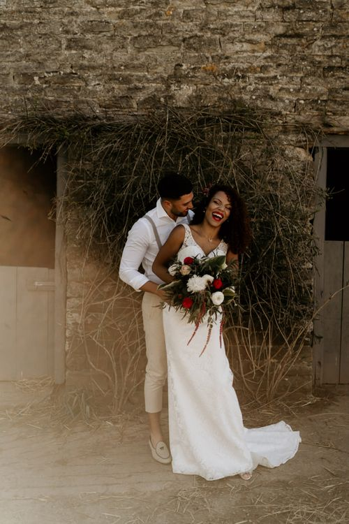 Black Bride with Afro Hair in a Lace Wedding Dress and Groom in White Shirt and Braces Laughing