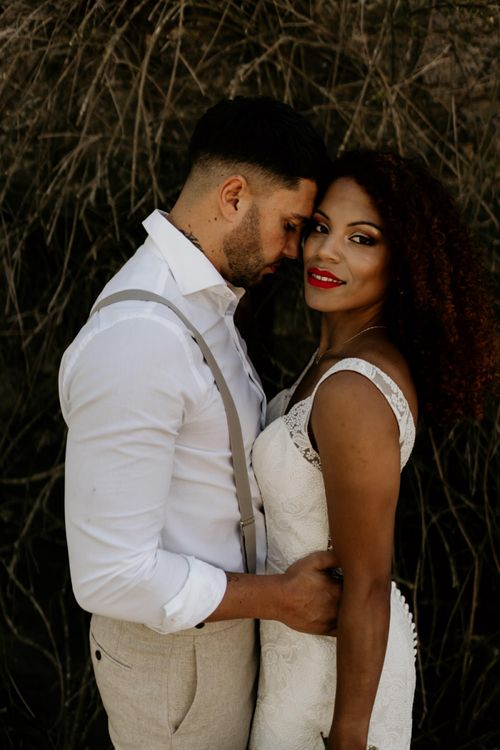 Black Bride with Afro Hair in a Lace Wedding Dress and Groom in White Shirt and Braces Embracing