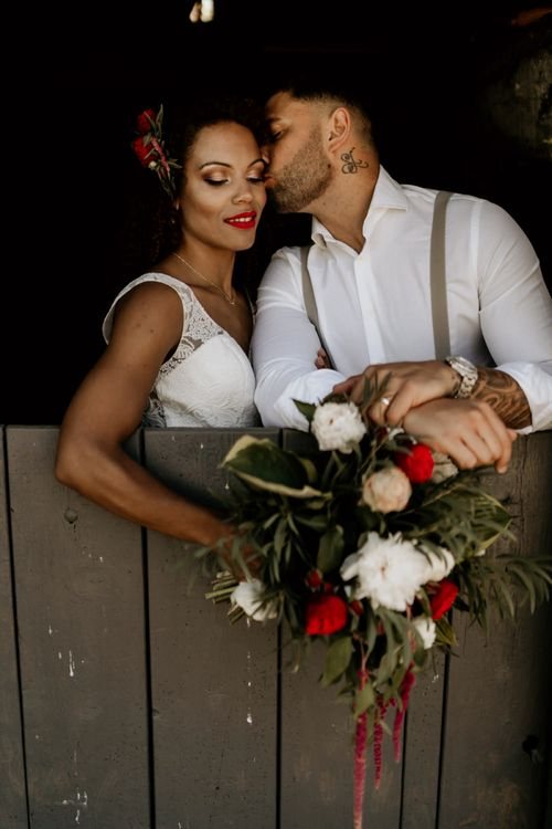 Black Groom in White Shirt and Braces Kissing Bride with Afro Hair in a Lace Wedding Dress