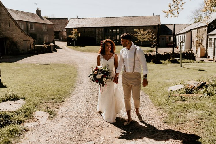 Black Bride with Afro Hair in a Lace Wedding Dress and Groom in White Shirt and Braces Walking Through the Barn