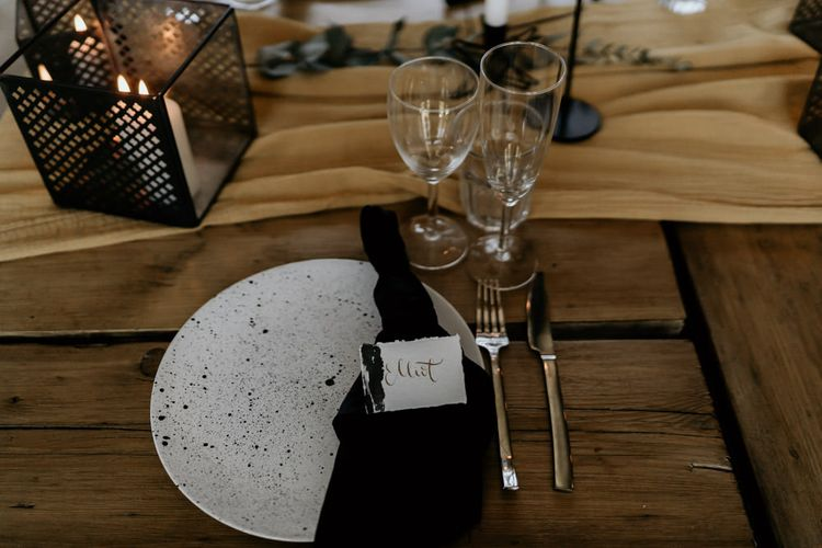 Elegant Place Setting with Speckled Tableware, Black Table Linen and Calligraphy Name Place Card